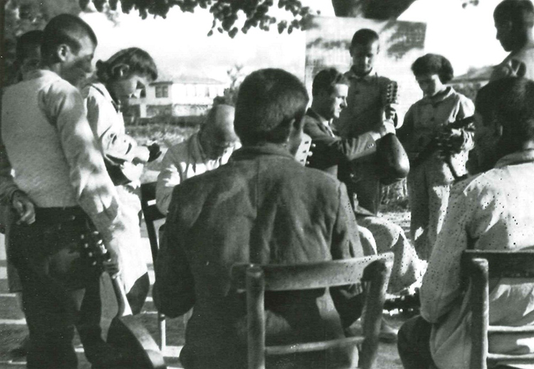 Students learning outdoors how to play the mandolin at the Akpınar Village Institute